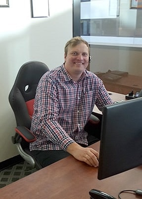 man smiling and sitting at the desk